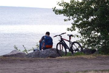 Велосипедист сидит рядом с велосипедом на берегу озера