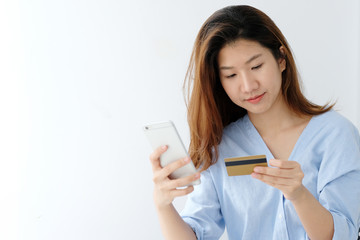 Young asian woman holding credit card and using smart phone for shopping online, business and technology concept, online payment, digital money