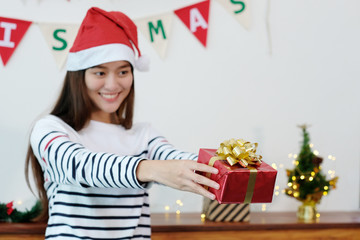 Young cute asian girl smiling and holding Christmas gift boxes at Christmas celebration party