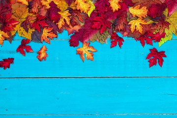 Blank antique rustic teal blue background with colorful autumn leaves border; wooden fall sign with copy space