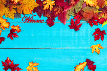 Welcome sign with color autumn leaves border hanging on antique rustic teal blue wood background; seasonal background with copy space