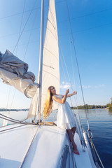 portrait of happy toothy smiley pretty girl with white dress and long curly blonde hair standing on yacht at summertime. standing on boat and looking at camera