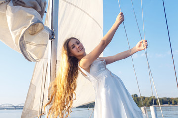 portrait of happy toothy smiley pretty girl with white dress and long curly blonde hair standing on yacht at summertime. looking at camera with toothy smile