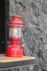 Red vintage kerosene oil lamp on wooden counter.
