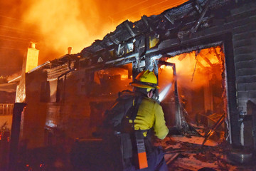 Santa Barbara County Firefighter spray water on flames at a home in Goleta