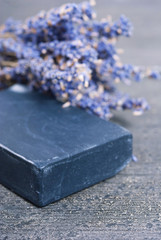 organic soap and a bouquet of dried lavender flowers on dark wooden
