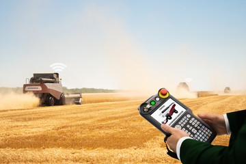 Etiqueta Engomada - Man with teach pendant device. Programming of self driving combine harvester. Internet of things in agriculture.