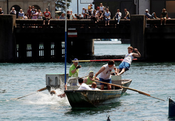 Participant falls from the back of a boat after using a lance to push a competitor from another boat during the traditional Schifferstechen event in Zurich