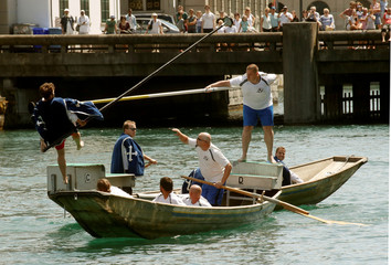 A participant standing on the back of a boat uses a lance to push a competitor from another boat during the traditional Schifferstechen event in Zurich