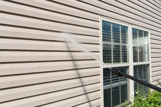 Power washing. House wall siding cleaning with high pressure water jet.