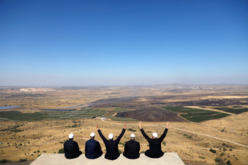 Israeli Druzes sit together watching the Syrian side of the Israel-Syria border on the Israeli-occupied Golan Heights, Israel