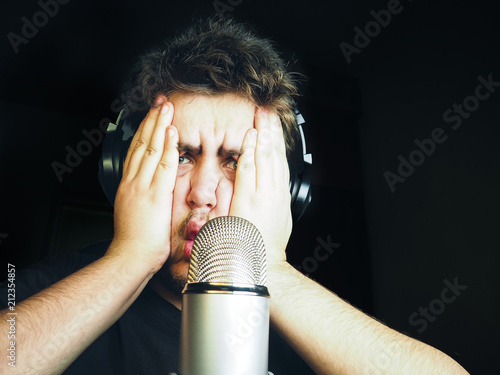 Young bearded man plays video games with mic for voice and