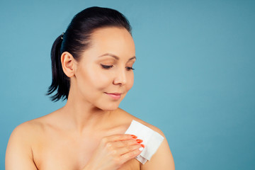 portrait of a beautiful and young woman with fresh and clean skin uses wet wipes on a blue background in the studio