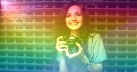 Vintage film photo of teenager photographer covered with raindow light leak