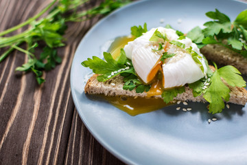 Homemade poached eggs on toast with fresh herbs and pepper