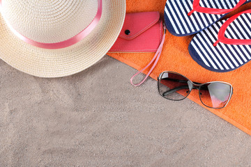 Beach accessories. Flip-flops, hat and glasses on an orange towel on the sea sand. Top view
