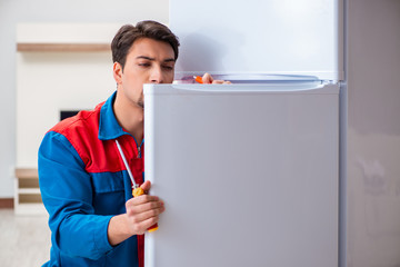 Professional contractor repairing broken fridge