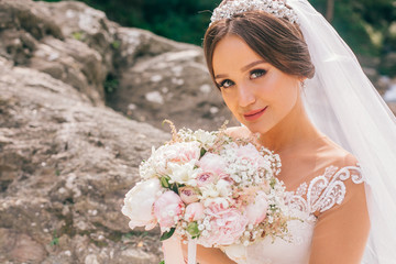 Beautiful bride walking on a fast river in the mountains. Wedding dress disperse of wind. Beauty portrait of a bride around amazing nature.