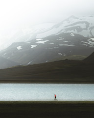 Person jogs in front of enormous mountain peaks