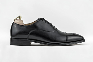 Generic unbranded black brogue show with shoetree in a white studio.