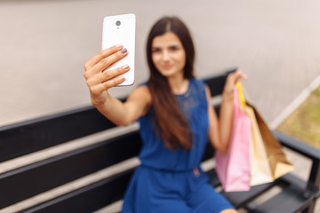 selfie with shopping on the street, a girl near the supermarket with packages, a woman sitting on a bench and waiting for a taxi