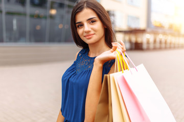 girl after shopping on the street, a Portrait of a woman holding paper bags, near the store