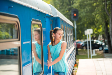 Young and happy woman pulling face out the train door looking for somebody at the railway station