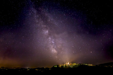 Starry night sky above the famous medieval town of San Gimignano, in Tuscany (Italy)
