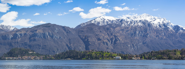 Overview of Lake Como with Bellagio. In the background snowy mountains and blue sky with small white clouds.