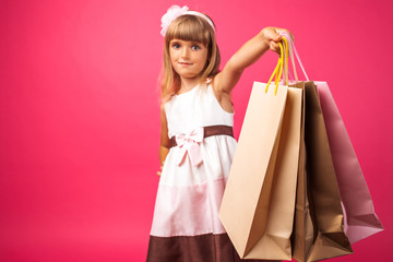 Shopping girl holding paper shopping bags on pink background, happy buyer, birthday gifts