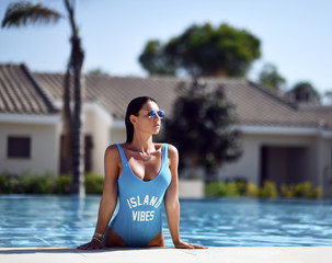 beautiful tanned woman in blue swimwear relaxing in swimming pool spa near expensive villa on hot summer day