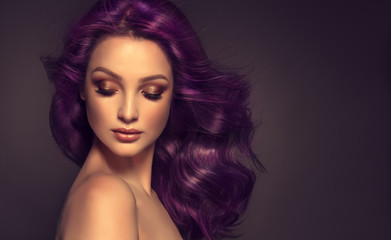Beautiful model girl with long purple curly hair . Care products ,hair colouring .  Treatment, care...