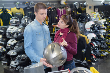 customer chooses moto equipment in motorcycle store