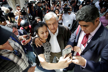 Mexico's president-elect Andres Manuel Lopez Obrador poses for a selfie with supporters as he arrives for a meeting with his new cabinet in Mexico City