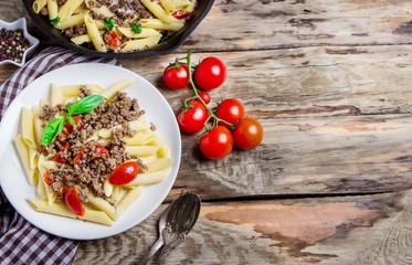 Pasta with tomatoes and meat on wooden background.