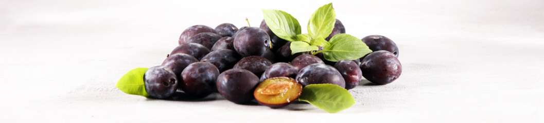Plums on white stone background. Half of blue plum fruit. Many beautiful plums with leaves.