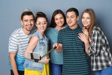 Young happy friends taking selfie against grey background