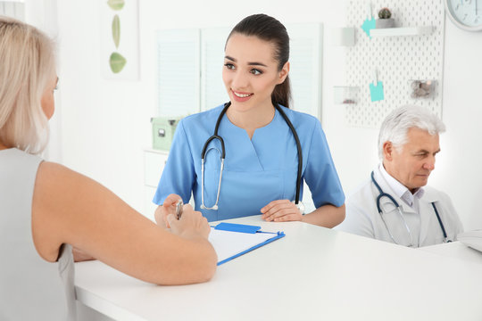 Young female doctor working with client at reception desk in hospital
