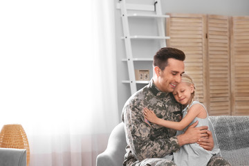 Young man in military uniform with his little daughter on sofa at home