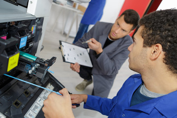 young apprentuce fixing office printer with teacher
