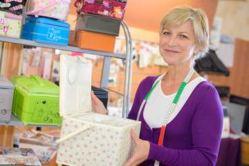 mature woman chooses vanity-case at shop