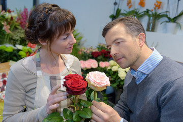 Florist looking at roses with customer