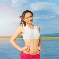 Young fitness woman standing by the sea on sunny summer day frowning. Natural lighting, square format image.