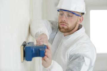 builder hand sanding interior wall for restoration