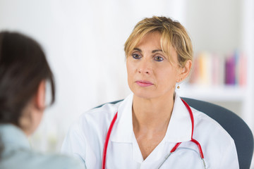female doctor listening to patient during consultation
