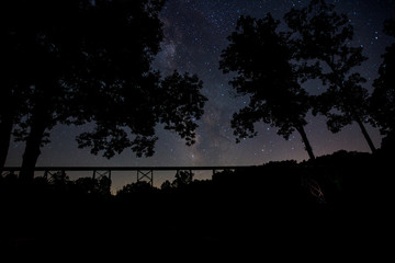 The Milkyway galaxy shining bright over an abandoned railway trestle in the midwest