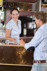 businessman talking to barmaid in a bar