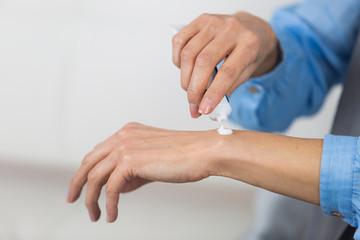 senior attractive woman spread cream on her forearm