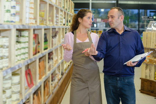 Manager instructing worker in store