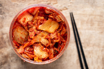 Kimchi cabbage in a bowl with chopsticks for eating, Korean food